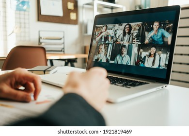 Woman has video call with her teammates using laptop.  White loft workspace. Close-up
