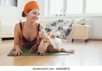 Woman has yoga practice at home but dog try to play with her