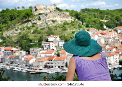 Woman with hat admiring cityscape. Novigrad, Croatia