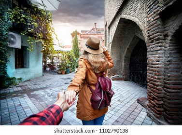 Woman in hat and brown jacket leading man to the narrow street in old, Georgia