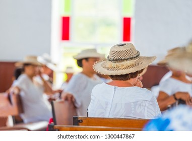 Woman in a hat in a catholic church in the service, Rarotonga, Aitutaki, Cook Islands. With selective focus. Back view