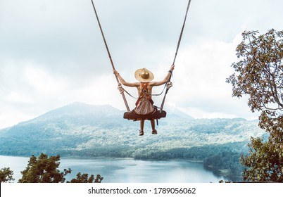 Woman with hat enjoying freedom on a swing in Bali, Indonesia. Life, adventure and peaceful feelings