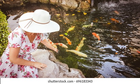 Woman with hat feeding the fish