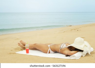 Woman with hat and glass of cocktail is lying on the beach