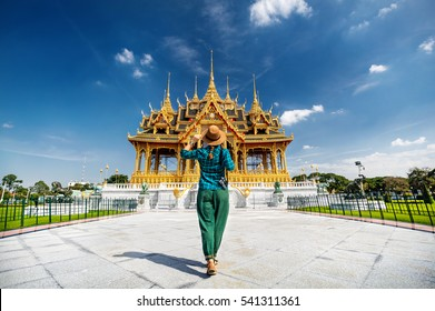 Woman in hat and green checked with photo camera going to the Ananta Samakhom Throne Hall in Thai Royal Dusit Palace, Bangkok, Thailand