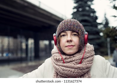 Woman in a hat and headphones listening to music and dancing on the street