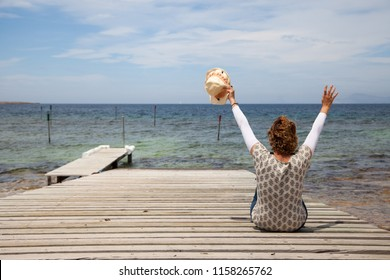 Woman with a hat and her arms raised up sitting on her back on the dock of a wooden pier by the sea