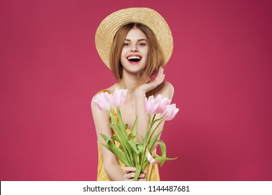 woman in a hat holding flowers smiling