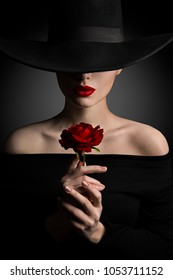 Woman in Hat holding Rose Flower in Hands, Fashion Model Beauty Portrait, Red Lips and Black Wide Brim Hat