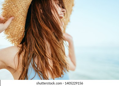 woman with hat laughs at sea ocean nature summer heat