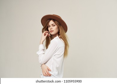 woman in a hat in a light suit looks at the camera