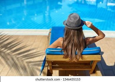 Woman in hat lying on a lounger near the swimming pool at the hotel, concept summer time to travel