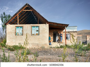 Woman with hat and man in checked shirt on the ruined old house in the village