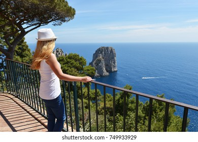 Woman in hat near fence in mountains