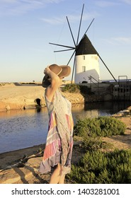woman with hat next to the salt flats and a mill in the Mar Menor, Murcia, Spain, pamela brown, holidays, milf, holidays,