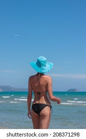woman in hat on the beach in the summertime