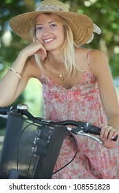 Woman with hat on a bicycle