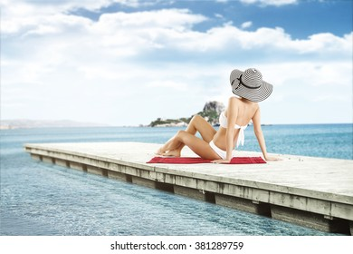 woman in hat on red towel and pier