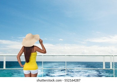 Woman in hat on ship desk looking to horizon sea water trail