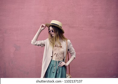 woman in a hat, pink wall