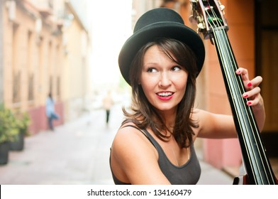 Woman in hat playing double bass on the street  of european city