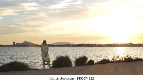 woman in hat playing with a handkerchief in the wind by the sea at sunset, , woman with hat next to the salt flats  in the Mar Menor, Murcia, Spain, holidays, milf, holidays,
