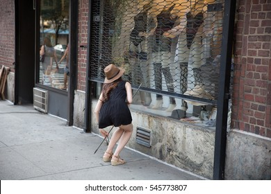 woman in hat pulling down gate over storefront window display with mannequins