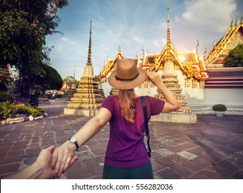 Woman in hat and purple t-shirt leading man by hand to the Wat Pho famous temple in Bangkok, Thailand.