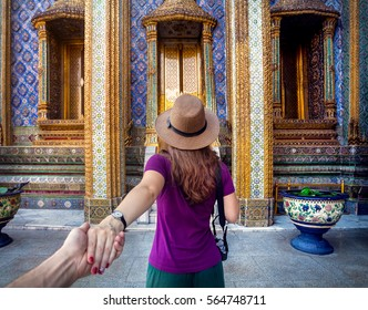 Woman in hat and purple t-shirt leading man by hand to the Wat Phra Kaew famous temple in Bangkok, Thailand