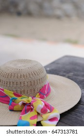 Woman hat put on the wood table at the beach, for holiday, vacation