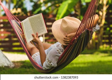 Woman with hat reading book in colorful hammock in tropical garden while relaxing in vacation.