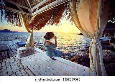 Woman in hat relaxing by the sea in a luxurious beachfront hotel resort at sunset enjoying perfect beach holiday vacation in Bodrum, Turkey. Outdoors Seascape Summer Travel Concept