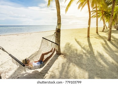 Woman in hat relaxing on hammock on the beach and enjoying sunset. Travel and vacation concept.