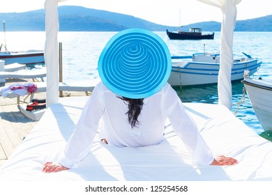 Woman in hat relaxing on luxury white bed at the sea
