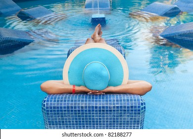 Woman in hat relaxing on swimming pool bed