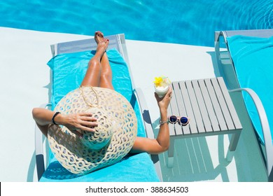 Woman in hat relaxing at the poolside with pina colada cocktail