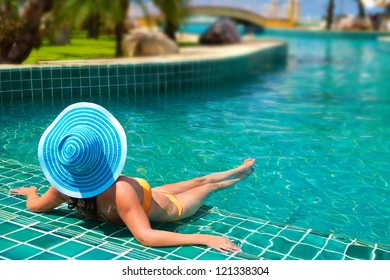 Woman in hat relaxing at swimming pool in Thailand