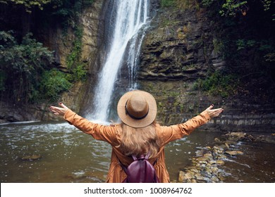 Woman in Hat rise her hand near waterfall in Botanical Garden in Tbilisi, Georgia
