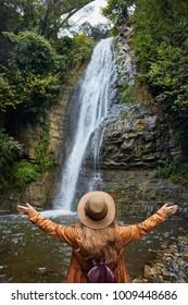 Woman in Hat rise her hand near waterfall in Botanical Garden in Tbilisi, Georgia