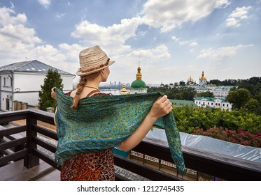Woman in hat with scarf looking to the church with golden domes at Kiev Pechersk Lavra Christian complex. Old historical architecture in Kiev, Ukraine