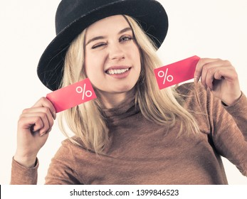 Woman in hat showing tag with shopping sale percentage sign enjoying cheap clothing. Female wearing stylish outfit.