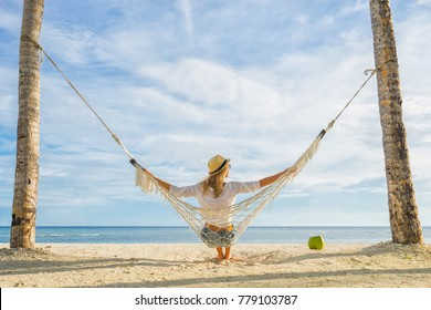 Woman in hat sitting in hammock on the beach. Travel and vacation concept.