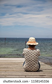 Woman with a hat sitting on her back on the dock of a wooden pier by the sea