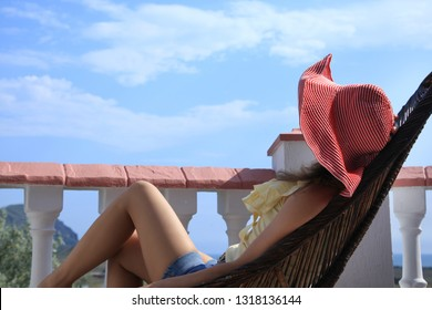 A woman in a hat sitting on a wicker chairs, looks into the distance from the balcony. Unrecognizable, close-up.