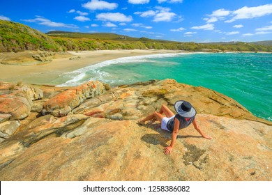 Woman in hat sunbathing on the rocks of Waterfall beach in Denmark, Western Australia. Caucasian tourist looking Great Southern Ocean in William Bay NP. Summer destination in Australia.