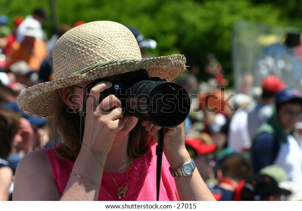 Woman in hat taking a photo
