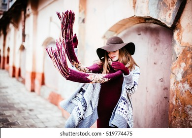 woman in the hat throws a red scarf aside