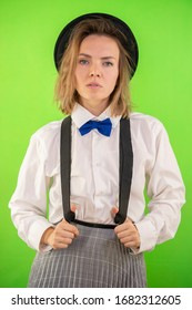 Woman in hat tie bow-tie suspenders and white shirt. Business woman concept. Woman in man's clothes.