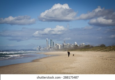 Woman with hat walks a dog along a windswept beach on This Spit on the Gold Coast in Queensland, Australia. It is a sand bar off the coast of Southport. Skyscrapers in distance, All logos removed.