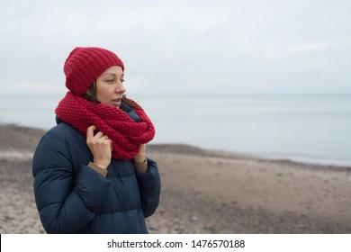 Woman in a hat walks near the sea in autumn